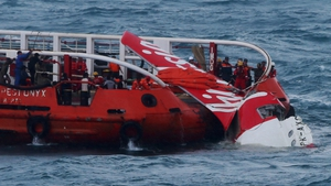 A search and rescue team pulls AirAsia wreckage onto a ship at sea
