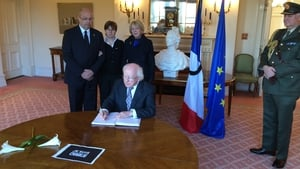 President Higgins signs the book of condolences at the French embassy