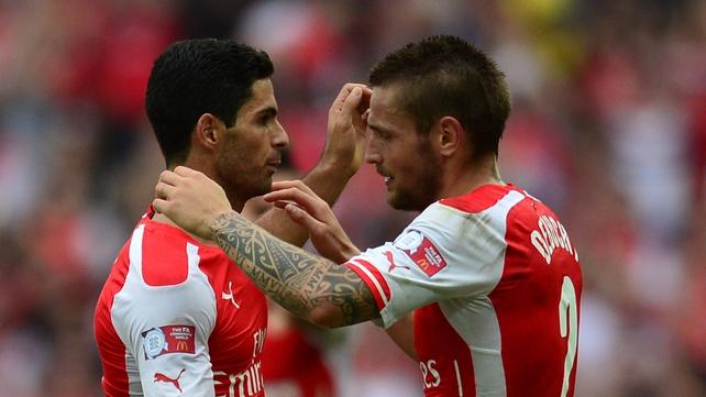Mikel Arteta embraces Mathieu Debuchy during happier times