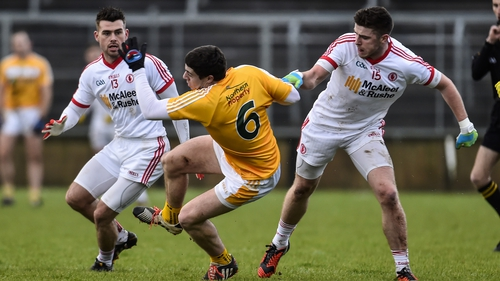 Antrim's Declan Lynch takes a fall under pressure from Tyrone's Darren McCurry and Connor McAliskey