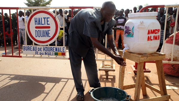 A man washes his hands in the village of Kouremale near the border with Guinea in November