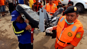 Indonesian rescue personnel carry a wrecked seat from the AirAsia Flight