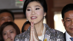 Former Thai prime minister Yingluck Shinawatra greets in the traditional way as she arrives to answer questions to the National Legislative Assembly during impeachment proceedings against her