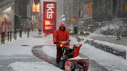 A worker clears the street in front of the TKTS booth in Times Square while heavy snow falls in New York