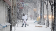 A man shovels snow from a footpath as snow falls in Brooklyn