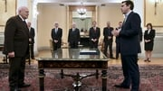 Alexis Tsipras (R) faces Greece's President Karolos Papoulias (L) as he is sworn in as Greek Prime Minister