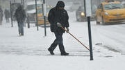 A man shovels snow from a footpath as snow falls in New York