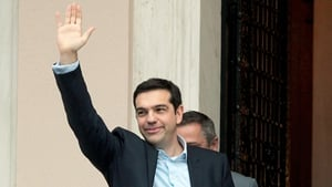 Alexis Tsipras waves on his way into the prime minister's offices in Athens