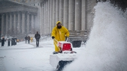 A worker clears the pavement near Foley Square during the snow storm in New York