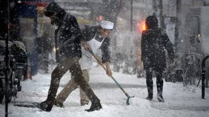 A man shovels snow from a pavement as the storm arrives in New York
