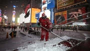 Worker removes the snow on a street following road closures in Times Square