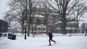 A skier makes her way down a street in Cambridge, Massachusetts