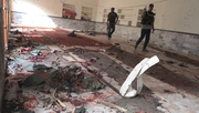 Pakistani security officials inspect the scene of the suicide bomb blast