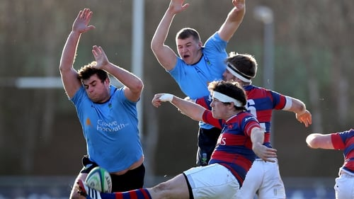 UCD's Liam Hyland and Ross Moloney charge down Sam Cronin of Clontarf