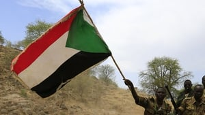 Sudanese soldiers wave the national flag