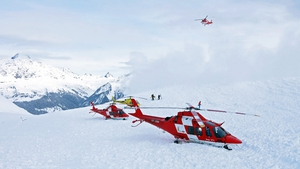 Rescue helicopters and rescue workers on duty after an avalanche  on the Piz Vilan mountain