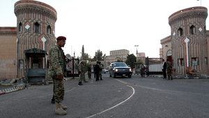 Members of the Huthi group, wearing army uniforms, stand guard outside the presidential palace