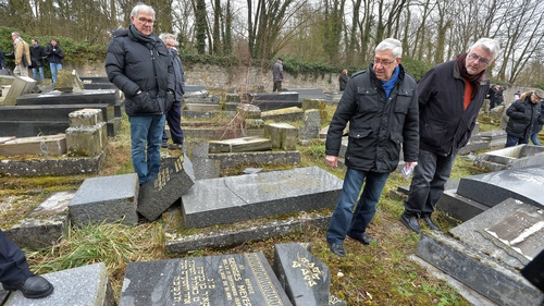 Members of the Jewish community look at the broken tombstones in Sarre-Union