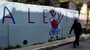 A man passes by a wall covered with graffiti reading 'Alexis the Great' in central Athens