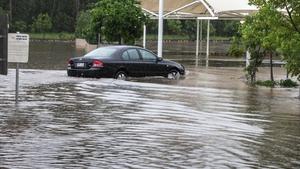 A car drives through flood water in a shopping centre carpark in Brisbane