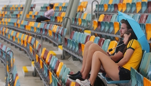 Fans wait for the rain to clear during the Cricket World cup match between Australia and Bangladesh at The Gabba, in Brisbane, Australia