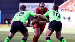 Scarlets' Phil John is tackled by Munster's Ian Keatley and Denis Hurley