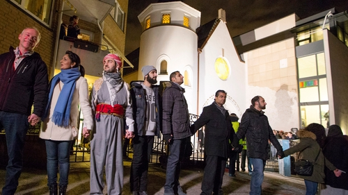 Jews and Muslims hold hands as they join in a ring of solidarity around the synagogue in Oslo, Norway