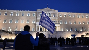 A man holds a Greek flag in front of the Greek parliament in Athens as people gather in support of their government