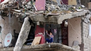 A girl sits among the rubble of destroyed buildings in Al Shejaiya neighbourhood in the east of Gaza