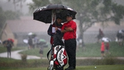 Patrick Reed and his caddie take shelter from the rain