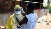 A health worker prepares to remove a corpse from a house in Freetown, Sierra Leone