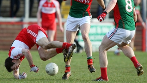 Derry's Daniel McKinless takes a tumble under pressure from Mayo players