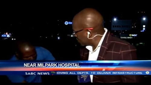 The video shows two men pacing around reporter Vuyo Mvoko while he speaks to the camera, before a scuffle ensues