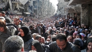 Residents queue for food aid in the Yarmouk refugee camp in Damascus, Syria