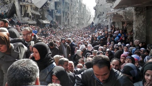 Residents wait in line to receive food aid distributed in the Yarmouk refugee camp on 31 January, 2014 in Damascus, Syria