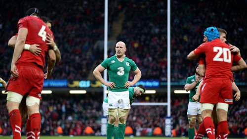 Ireland captain Paul O'Connell cuts a dejected figure as Wales players celebrate their 23-16 victory at the Millennium Stadium