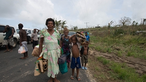 A family carries their belongings on the outskirts of Port Vila