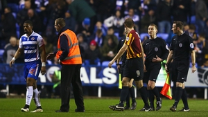 Garath McCleary of Reading walks off for half-time as James Hanson of Bradford City talks to referee Mike Jones
