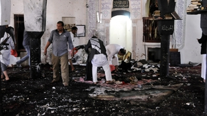 Members of Houthi militia inspect the scene at the al-Hashahush mosque