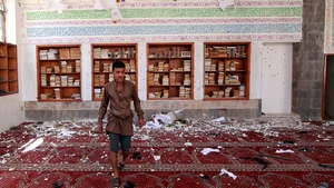 A man inspects the damage of a bomb blast at a mosque in Sanaa, Yemen