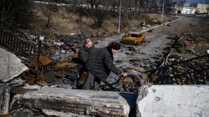 Men push a cart over a destroyed bridge near Donetsk airport in eastern Ukraine