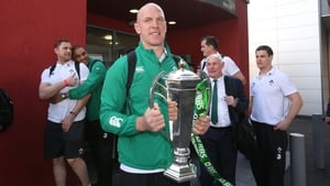 Paul O'Connell brings the Six Nations trophy back home through Dublin Airport, while Simon Zebo gives Jamie Heaslip a hug