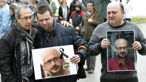Men hold up pictures of their colleague who died in the crash