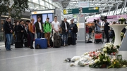 Visitors and travellers stand in a moment of silence at a memorial desk at the airport in Duesseldorf