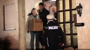 Investigators carry boxes from the home of Andreas Lubitz