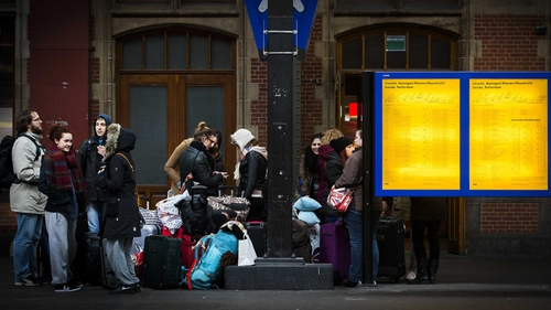 Rail passengers stand around during a major power outage at Amsterdam Central Station