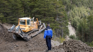 A gendarme watches a bulldozer clearing a path to the crash site near Seyne-les-Alpes