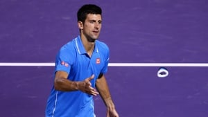 Novak Djokovic throws his wristbands to the crowd after his straight sets victory against John Isner