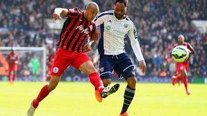 Bobby Zamora of QPR scores their third goal under pressure from West Brom's Joleon Lescott