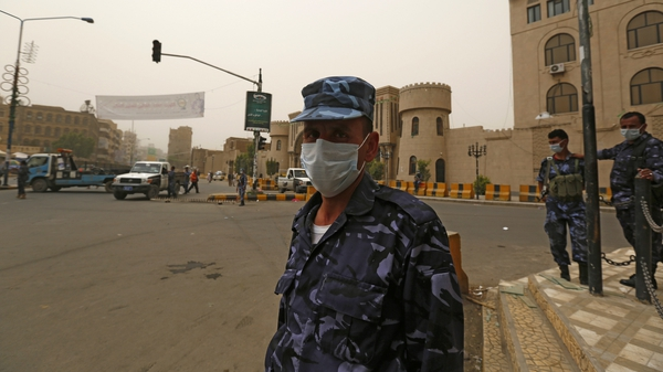 Yemeni policemen wear surgical masks to protect themselves from a sandstorm at a checkpoint in Sanaa